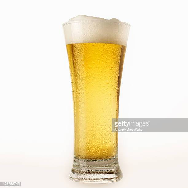 Glass of chilled lager beer with foam head