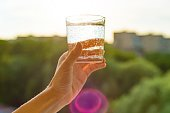 Glass of clear, ecology water in hand. Background sky, silhouette of the city, sunset.