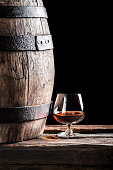 Glass of cognac and old oak barrel.