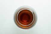A glass of cognac on a white background, top view