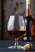 Glass of cognac on rustic ferruginous background