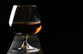 Glass of cognac on the dark wooden table. Black background