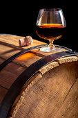 Glass of cognac on the vintage wooden barrel.