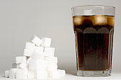 A glass of coke and a heap of sugar cubes