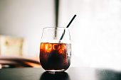 Black cold brew coffee with ice cubes in a glass. Hipster coffee shop. Minimalism drink photography