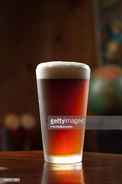 Glass of cold foamy beer on a bar