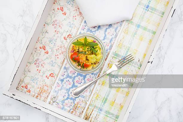 Glass of couscous salad and fork on tray
