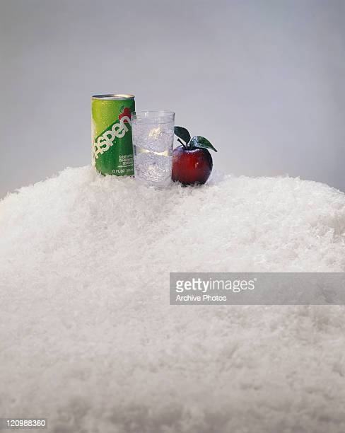 Glass of drink, tin can and apple on crushed ice