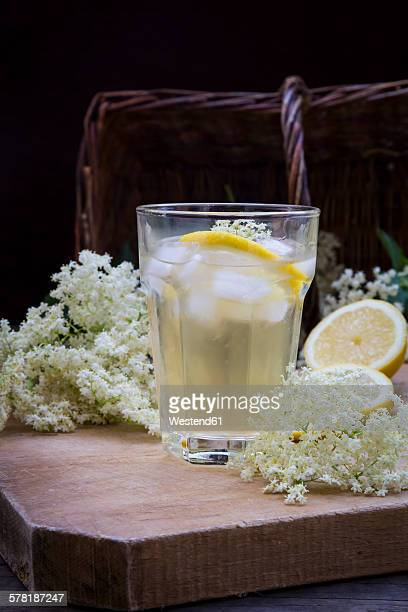 Glass of elderflower sirup with ice cubes and slices of lemon