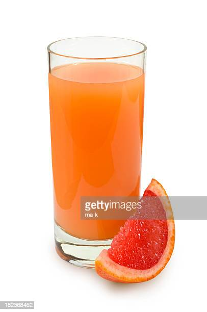 Glass of fresh squeezed grapefruit juice next to a wedge