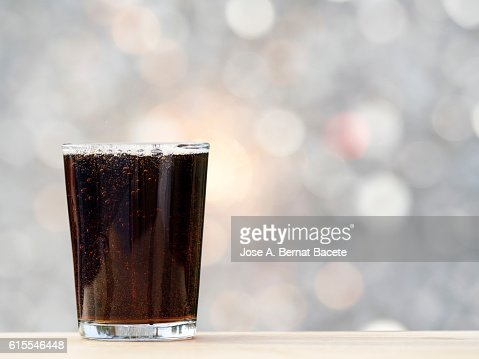 Glass of full glass with a refreshment of  cola illuminated by the light of the Sun