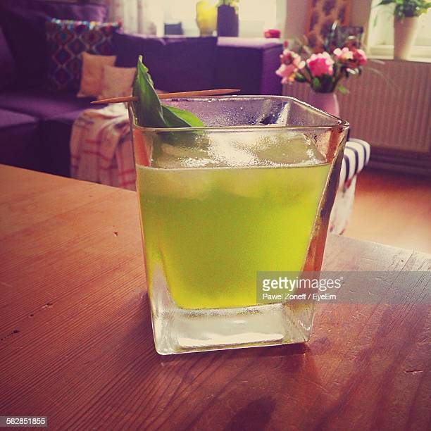 Glass Of Gin With Basil On Wooden Table