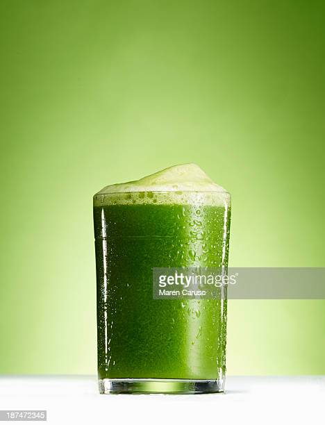 Glass of Green Juice in front of Green Background