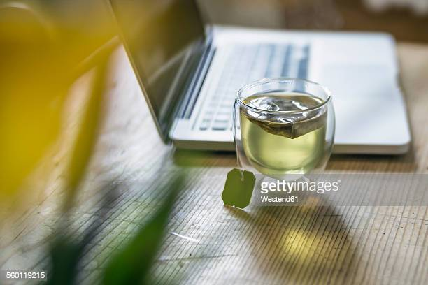 Glass of green tea beside laptop