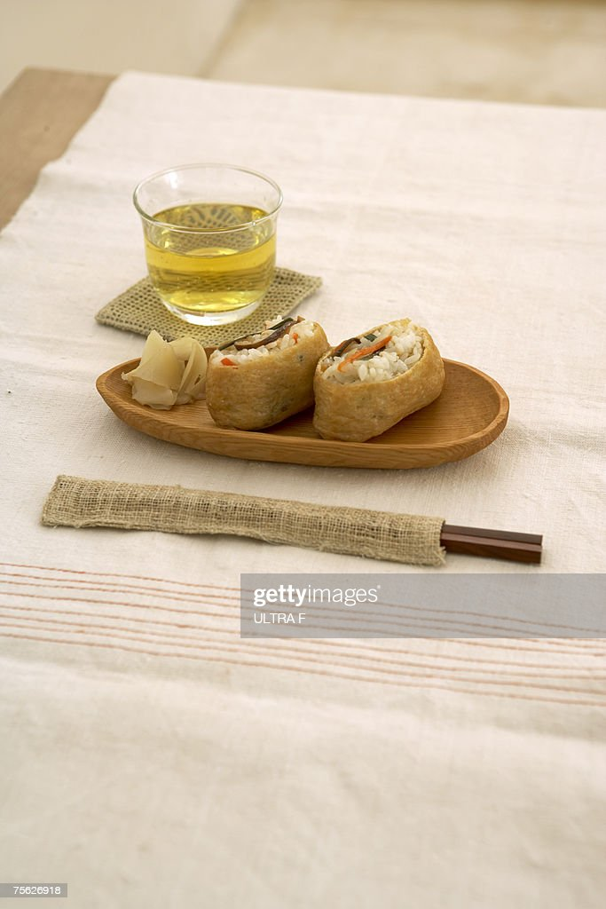 Glass of green tea with Japanese style food on wooden tray and chopsticks in burlap cover, on natural colour tablecloth : Stock Photo