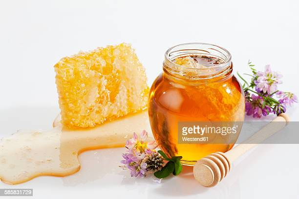 Glass of honey, honeycomb, honey spoon and wild flowers