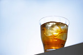 Glass of iced tea, blue background, copy space