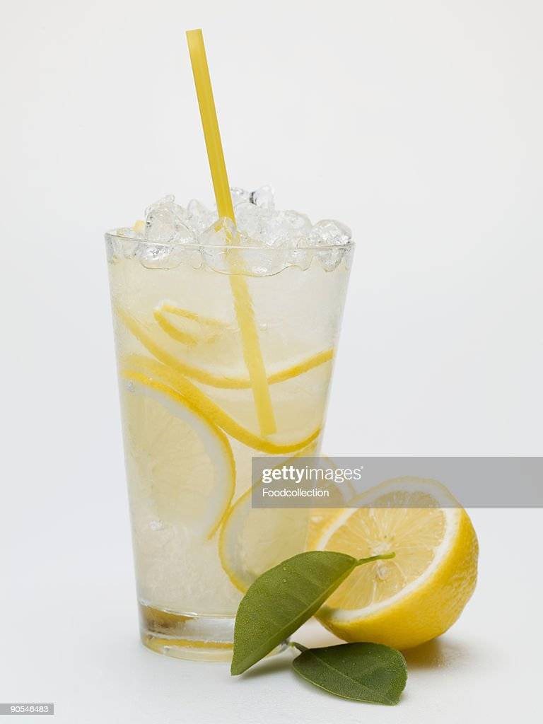 glass of lemonade with crushed ice and straw close up