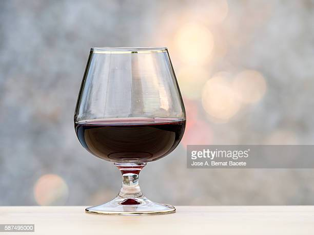 Glass of liquor fills on a table of wood illuminated by the light of the Sun