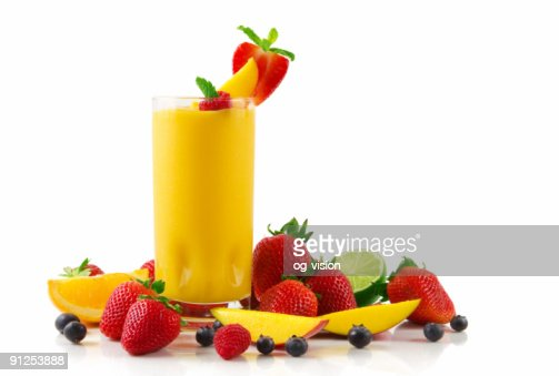 Glass of mango smoothie and fruits on a white background : Stock Photo