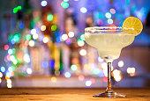 Glass of margarita cocktail on bar lights background.