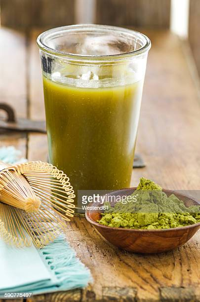 Glass of matcha tea, bowl with matcha powder and a tea whisk