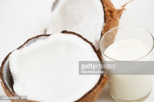 Glass of milk beside halved coconut, elevated view
