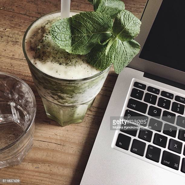 Glass of mint julep with laptop