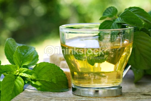 A glass of mint tea on a table covered in mint leaves : Stock Photo
