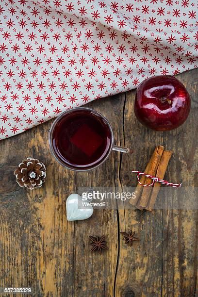 Glass of mulled wine, christmas bauble, apple, cloth, cinnamon sticks and cinnamon stars