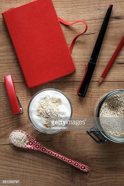 Glass of natural yoghurt with oak bran on a desk with office utensils
