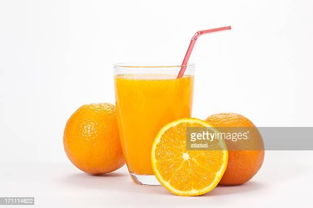 Glass of orange juice and three oranges over white backdrop