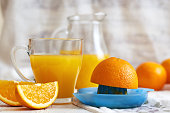 Plastic juicer with glass of fresh orange juice on white rustic wooden background. Copy space