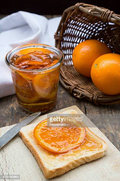 Glass of orange marmalade with orange slices and toast