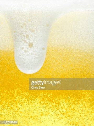 Glass of overflowing beer foam