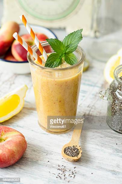 Glass of peach smoothie with lemon and chia