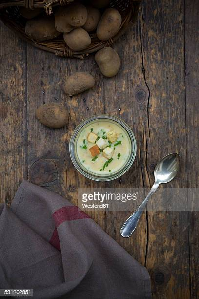 Glass of potato soup garnished with chives and croutons on wood