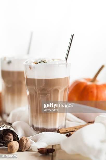 Glass of pumpkin spice latte Macchiato and spices on cloth