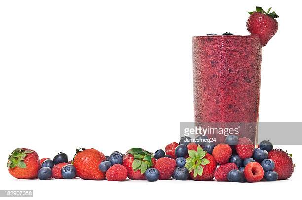 Glass of R red berry smoothie with various berries around
