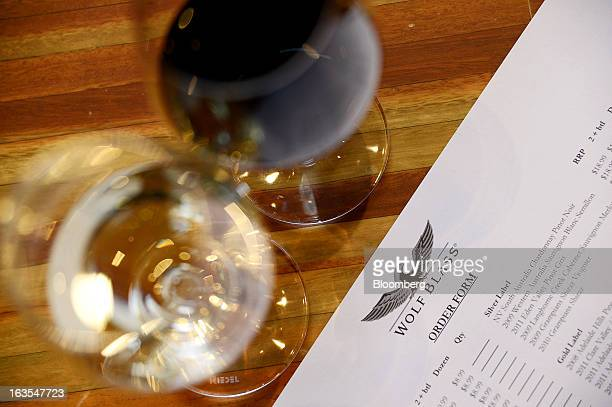 A glass of red and white wine are arranged for a photograph next to an order form at the tasting bar at Treasury Wine Estates Ltd's Wolf Blass winery...