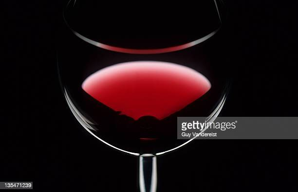 Glass of red wine against black background.
