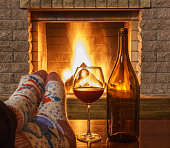 Glass of red wine and a bottle, Man's Feet in socks, near cozy fireplace, in country house, winter vacation, horizontal.