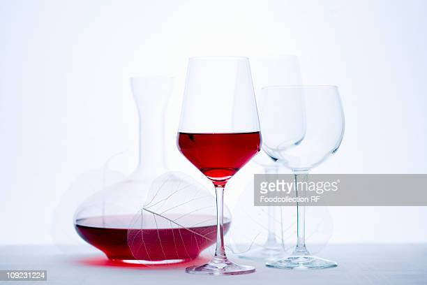 Glass of red wine, carafe and empty wine glasses, close-up