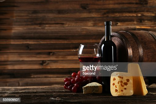 Copo de Vinho Tinto, queijo e uvas no fundo de madeira : Foto de stock