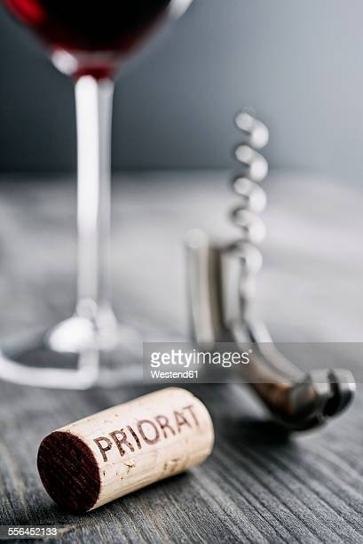 Glass of red wine, corkscrew and wine cork with the word Priorat