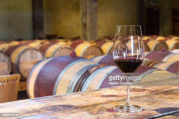 Glass of red wine in a winery cellar, New Zealand