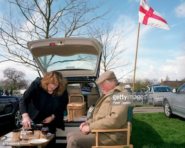 A glass of red wine is poured for a gentleman having a picnic in the car park before an England rugby match at Twickenham Stadium April 2001