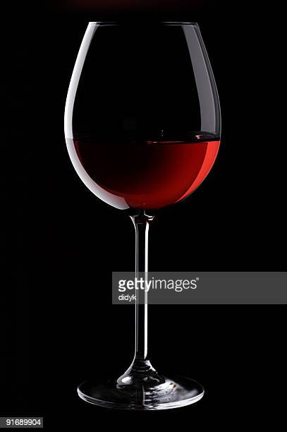 A glass of red wine on a black background