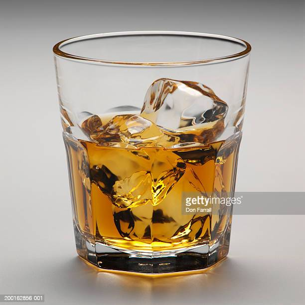 Glass of scotch with ice cubes, close-up