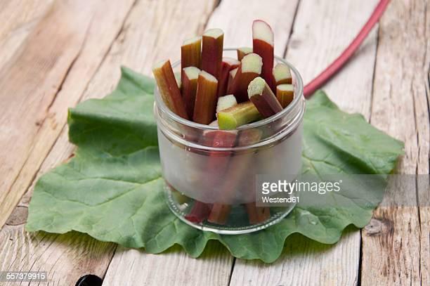 Glass of sliced rhubarb on rhubarb leaf and wood